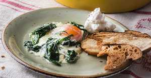 Presentation photo of Baked eggs with wilted spinach
